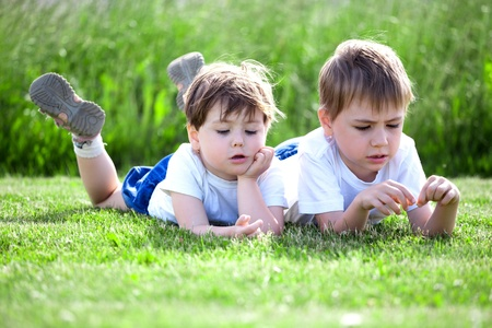 kiddies: Two cute preschool siblings lying on green grass with field in background.. Stock Photo