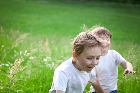 Two cute young preschool, child running and playing in green field. photo