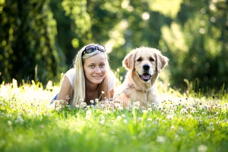 A girl and a dog laying together in grass photo