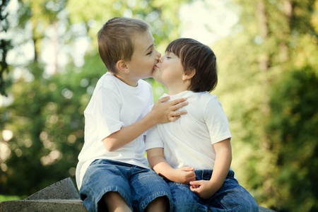 Cute young preschool boy and girl kissing outdoors with leafy, sunlit background. photo