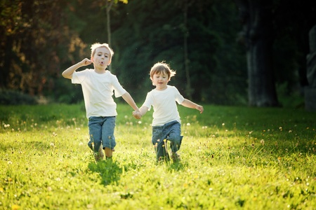 Young boy and girl holding hands and running in a sunny meadow.