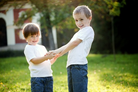 Cute young brother and sister holding hands and playing in garden; summer scene. photo
