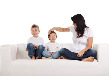 Young woman and two children on a white sofa. photo