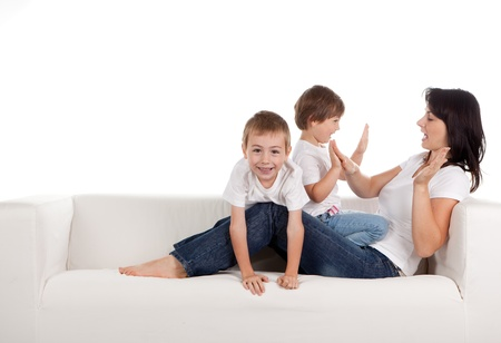 family couch: Women and children lying on a white sofa.  White background Stock Photo