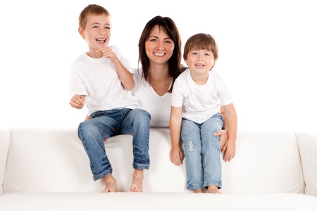 A smiling mother holds her happy pre-school children as they sit laughing on a white sofa. photo