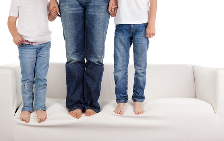 A young family wearing jeans standing on the sofa.