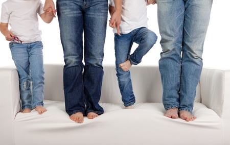 blue jeans kids: A young family wearing jeans standing on the sofa.