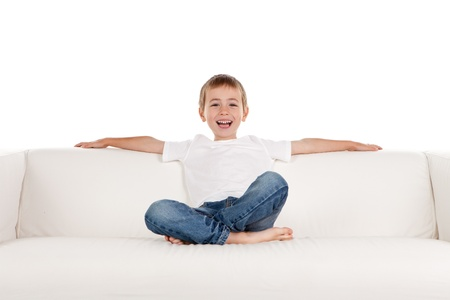 settee: Happy young boy relaxing on sofa, settee or couch; white studio background.