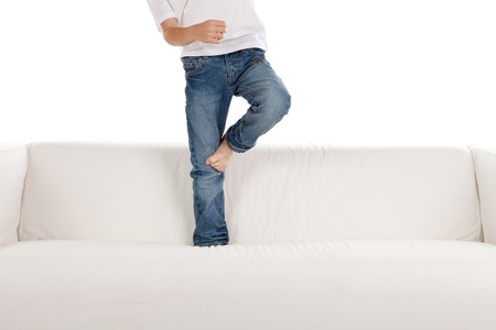 Legs of barefoot child in jeans stood on couch, sofa or settee; isolated on white background.
