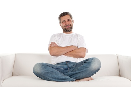 A man wearing casual jeans and t-shirt sits relaxing on a white sofa with his arms and legs crossed.