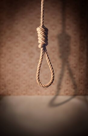 A noose hanging in a dark room. photo