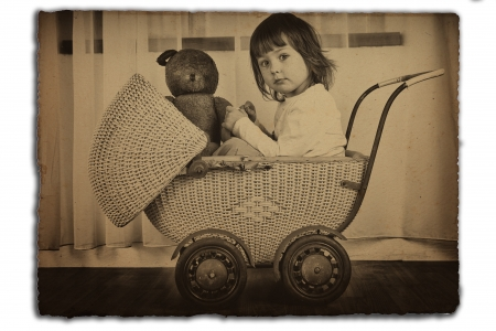 old photograph: Young girl in an antique wicker baby carriage with teddy bear.  Old sepia photo