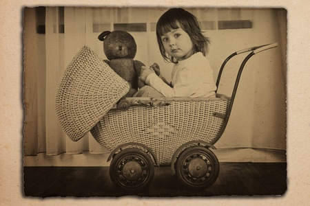 old fashioned sepia: Young girl in an antique wicker baby carriage with teddy bear.  Old sepia photo