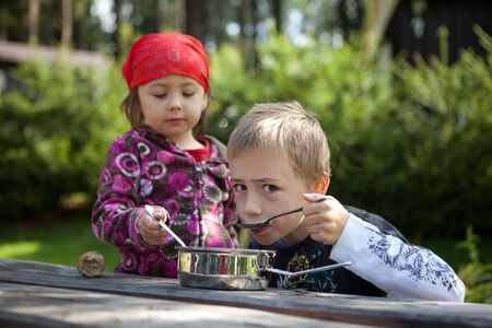 Two children camping and having a lunch outdoors. Stock Photo - 15331388