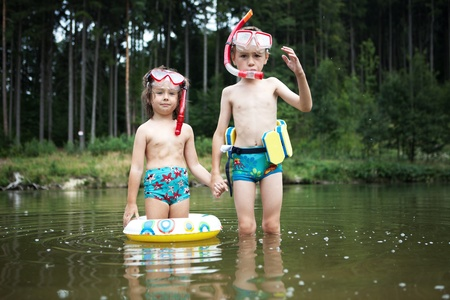floater: Two children swimming with floaters, masks and snorkels in a pond in a forest.