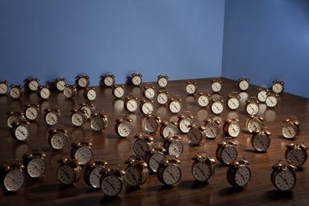 Many alarm clocks on a wooden floor. Art installation. Stock Photo