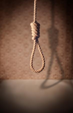 suffocate: A noose hanging in a dark room.