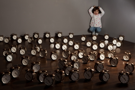 lots of: A girl in the corner of a room in which the floor is covered by alarm clocks.