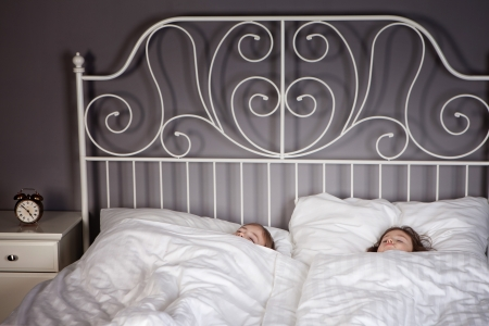 bedhead: Sister and Brother sleeping in their parents bed with an alarm clock set.