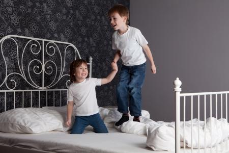 Jonge jongen en meisje spelen en springen op een bed. Stockfoto