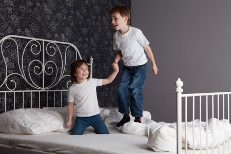 Young boy and girl playing and jumping on a bed.