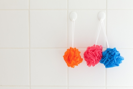 scrubbers: Three soft nylon body scrubbers hanging on the white tiles of a shower wall.