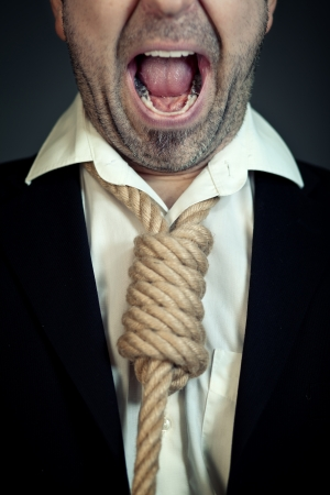 Unshaven businessman with a noose instead of a tie around his neck screaming. photo
