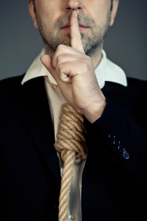 Businessman with rope noose around neck, holding quiet finger to mouth. photo