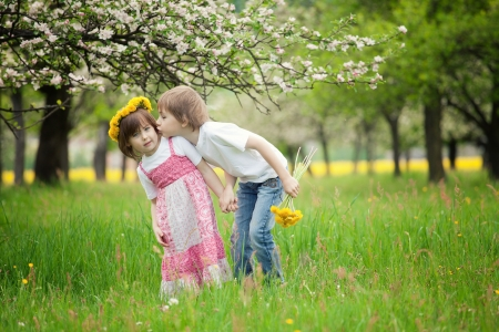 Two young children kissing in flowery meadow of long grass, girl wearing daisy flower crown. photo