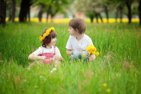 Young boy and girl or siblings sitting in bright green grassy field