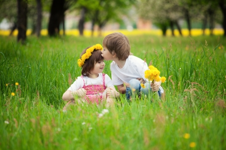 forehead: Two young children kissing in flowery meadow of long grass, girl wearing daisy flower crown.