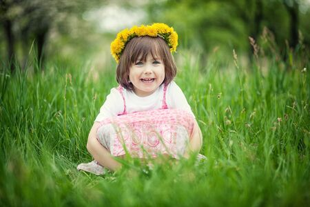 happily: Young smiling girl sitting in tall green grass.