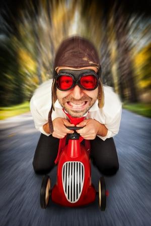 gente loca: Hombre en el sombrero y las gafas retro de carreras conduciendo en el coche de juguete a toda velocidad con el fondo borroso.