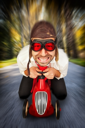 madness: Man in retro racing hat and goggles driving on toy car at speed with blurred background. Stock Photo