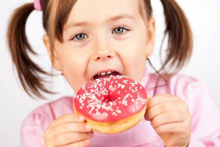 aliments droles: Fille mangeant un beignet collation malsaine. Banque d'images