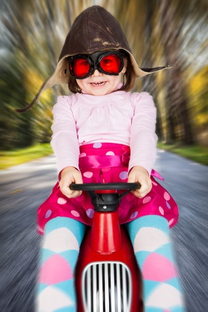 Girl in retro racing hat and goggles driving on toy car at speed with blurred background. Standard-Bild