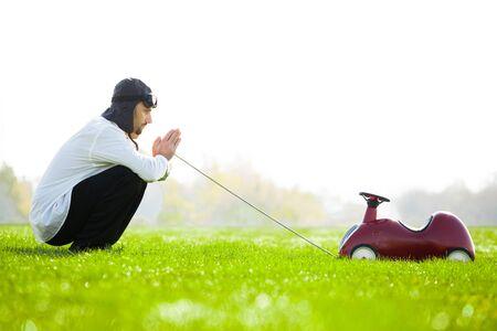 pull toy: Hombre en casco de carreras de estilo retro con el coche de juguete de plástico en campo verde.