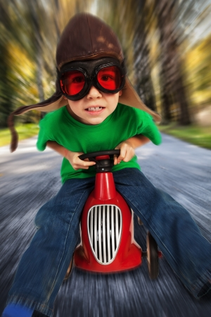 Boy in retro racing hat and goggles driving on toy car at speed with blurred background