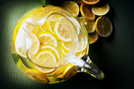 jugs: A pitcher of lemonade with slices of lemon and limes.