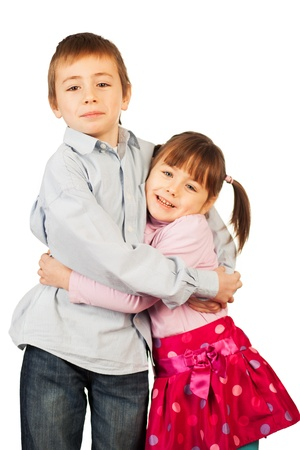 Smiling young brother and sister, both wearing white, in a hug   Isolated on a white background  photo