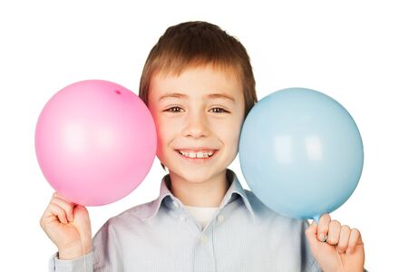 Portrait of happy boy holding blue and pink balloons next to head, white background