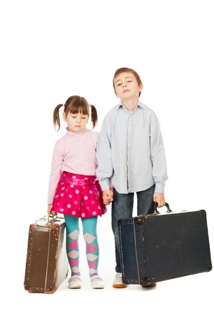 Two bored young children with retro suitcases, white background  photo