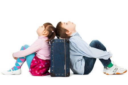 Young boy and girl sitting back to back against a suitcase their eyes shut  with  tiredness and boredom  photo