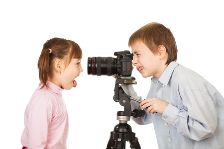 photographing: Portrait of young boy with digital camera on tripod photographing girl pulling funny face, white studio background