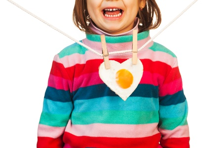 Young lady in colorful striped jumper with fried egg in heart-shape hanging like a necklace   photo