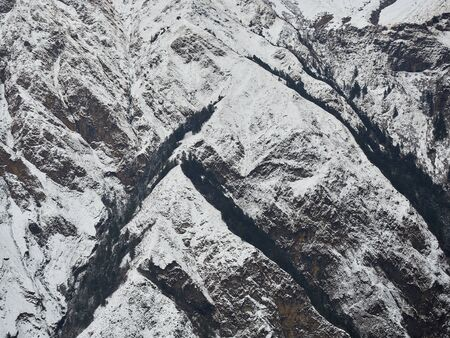 The rocky slopes of the mountain, covered with forest in the hollows and covered with the first snow, form a geometric pattern. Stok Fotoğraf