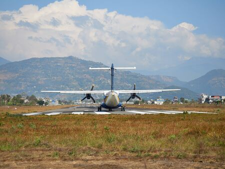 A plane of local, Nepalese airlines on the runway of the airport in Pokhara is preparing for take-off.