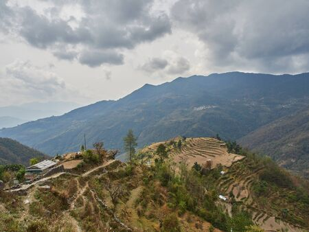 Harvested rice terraces on a hill in a remote village in the Himalayas. Cloudy autumn day. Nepal.