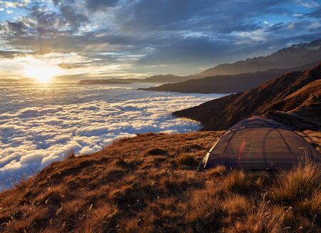 A small tent without an awning, on the edge of a high hill along the route to the eastern base camp of Mardi Himal. Stunning sea view of clouds at sunset