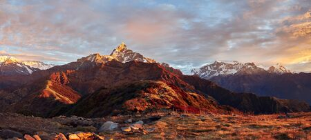 Panoramic view of the majestic Himalayan peaks - Machapuchare, Annapurna IV and Annapurna II, covered with clouds illuminated by the sunset. View from the Korchon mountain shelter